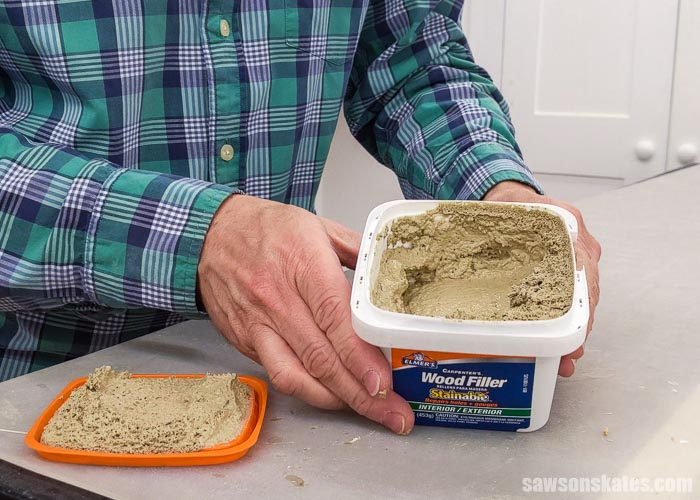 Holding an open container of Elmer's Stainable Wood Filler