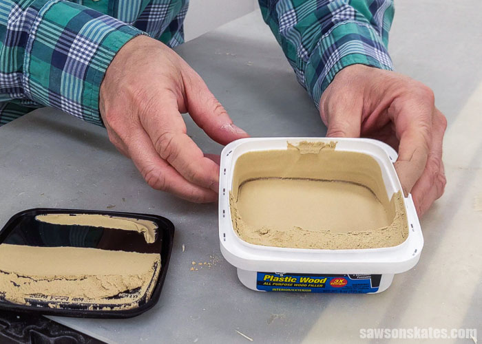 Holding an open container of DAP Plastic Wood