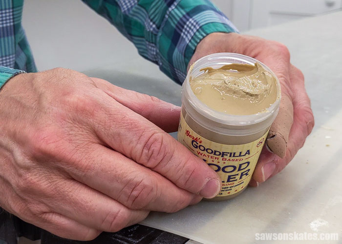 Holding an open container of Goodfilla Stainable Wood Filler