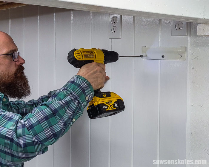 Using a drill to a attach a wall bracket for a wall-mount dust collector
