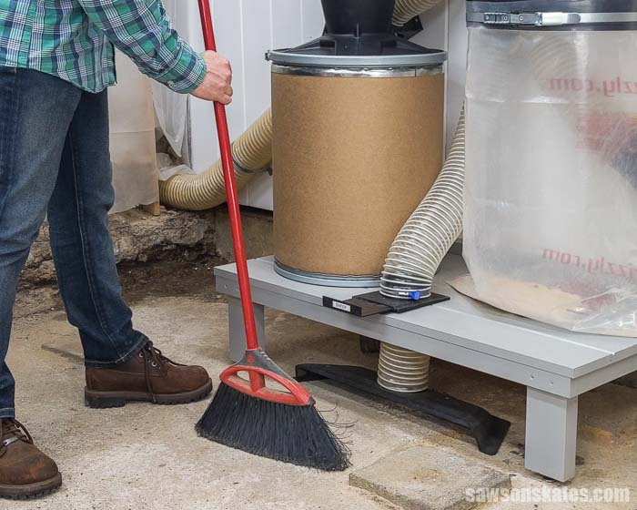 Using a broom to sweep sawdust into a floor sweep that is part of a small shop dust collection system