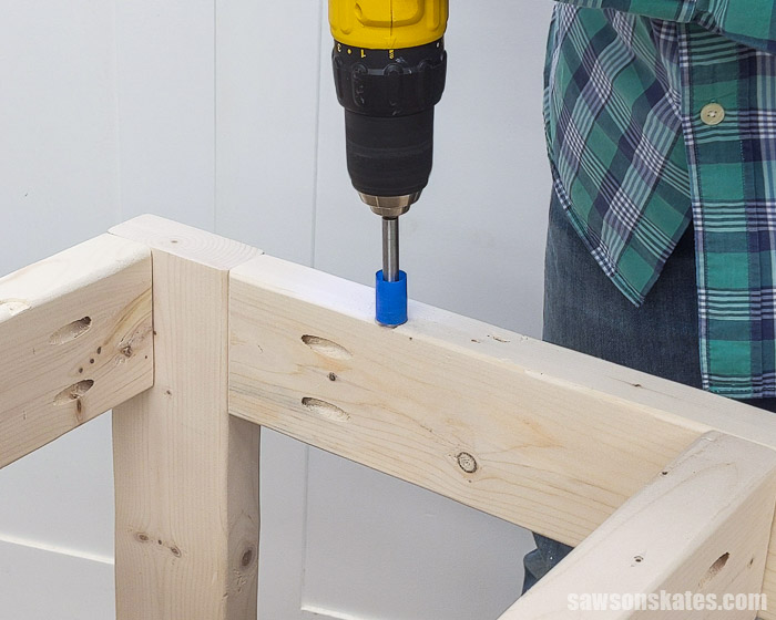 Drilling a hole for a table top fastener to attach the top on a DIY drill press stand