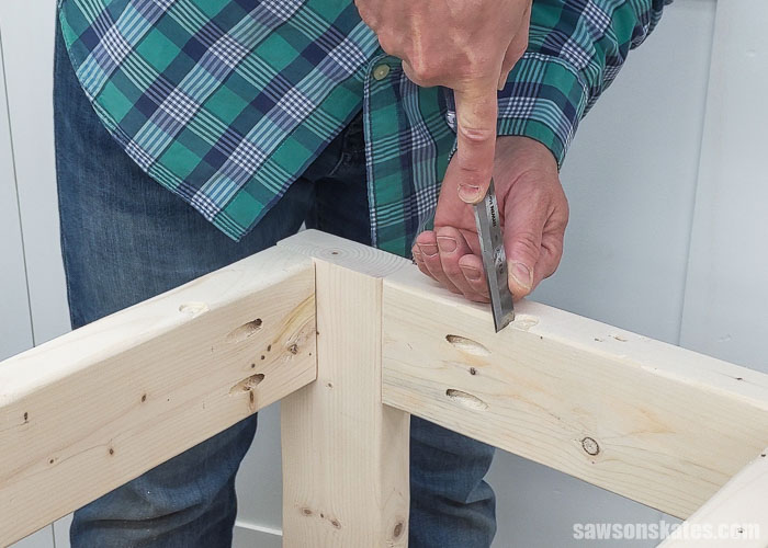 Using the a chisel to square the corners of a hole for a table top fastener that will be used to attach the top of a DIY drill press stand