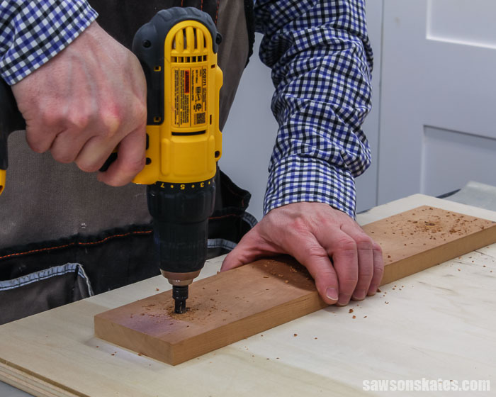 A drill making countersink holes in the base for a simple-to-make tilting DIY wood frame