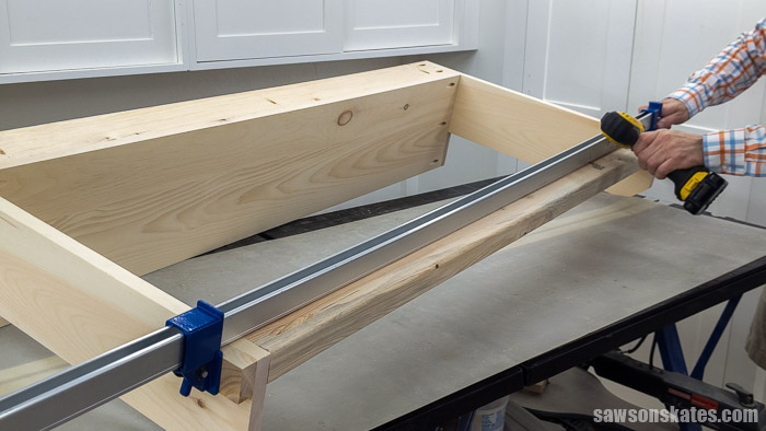Using a drill to attach the bottom rail of  a DIY garden tool storage rack